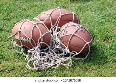 American football balls in net on field