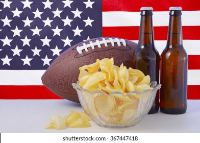 American football with beer and chips on white wood table with USA stars and stripes flag background.