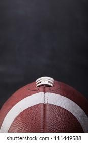 Ein amerikanischer Fußball mit einer Kreide im Hintergrund für Kopienraum.