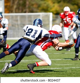 American football game. Running back dives for first down versus defender.