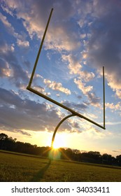 American football goal posts and end zone at sunset over dramatic cloudy sky