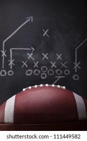 Ein amerikanischer Fußball und ein handgezeichnetes Chalkboard-Spiel.