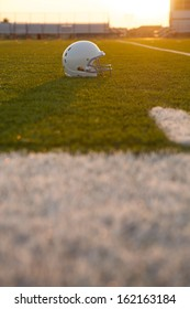 American Football Helmet Backlit on the Field at Sunset with room for copy