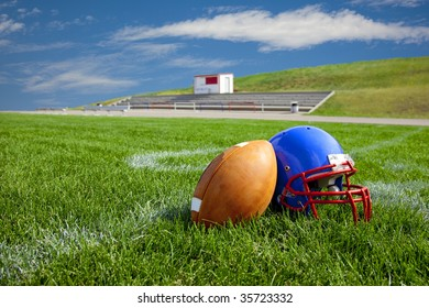 American Football and Helmet on a then 20 yard line over looking a small grandstand.