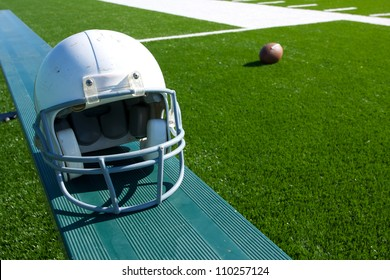 American Football Helmet on the Bench with the field and ball beyond