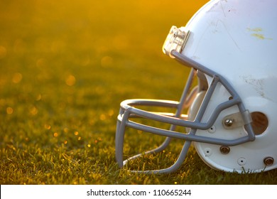 American Football Helmet on the Field with room for copy backlit by the setting sun