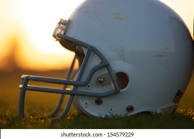 American Football Helmet on the Field backlit by the Sunset