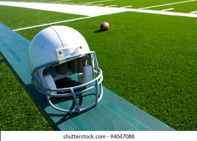 American Football Helmet on the Sideline Bench with field in the background