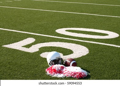 American football, helmet, and pom poms on field next to 50 yard line.