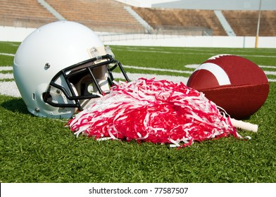 American football, helmet, and pom poms on field in stadium.