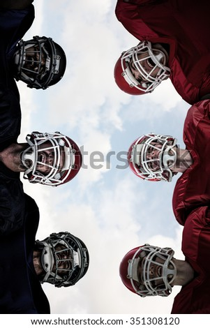 American football huddle against blue sky with white clouds