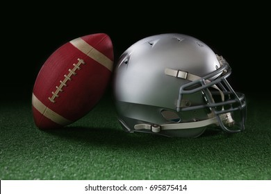 American football leaning on headgear against black background