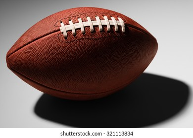 American football with lower half in shadow on white background