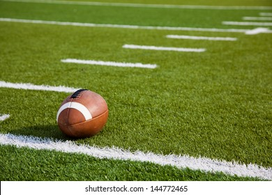 An American football on a green football field