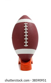 An american football on a kicking tee