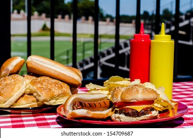American football party with cheeseburger, hot dog, potato chips, ketchup and mustard bottles and buns.  Football field in background.