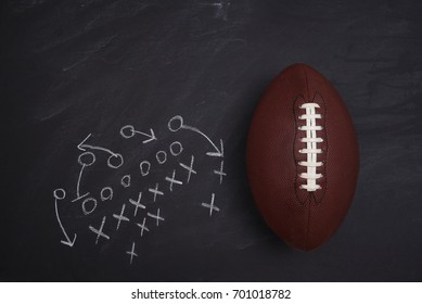 American Football and play diagram on a chalkboard. Top view with copy space.