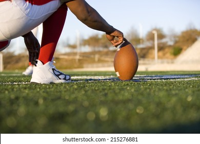 American football player attempting to kick field goal, teammate holding ball vertically against pitch (surface level)