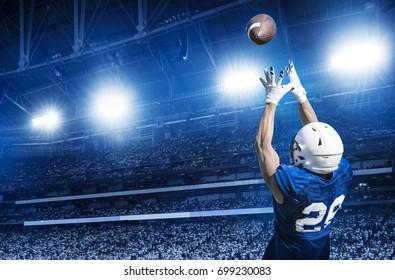 American Football Player Catching einen Touchdown Pass in einem großen Stadion.