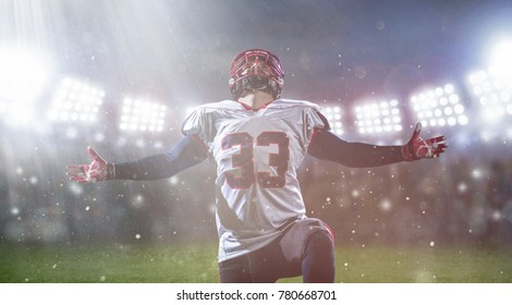 american football player celebrating after scoring a touchdown on the field of big modern stadium with lights and flares at night
