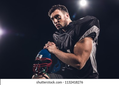 american football player with helmet looking away under spotlights on black