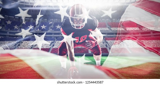 American football player in helmet taking position against full frame of american flag