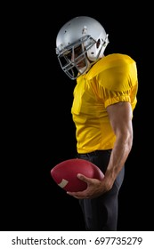 American football player holding a ball against a black background