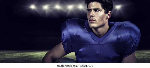 American football player holding helmet while looking away against rugby stadium
