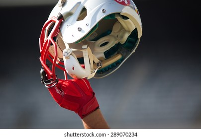 american football player holding up his  helmet - victory concept
