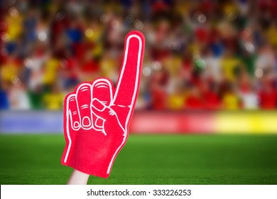 American football player holding supporter foam hand against rugby stadium