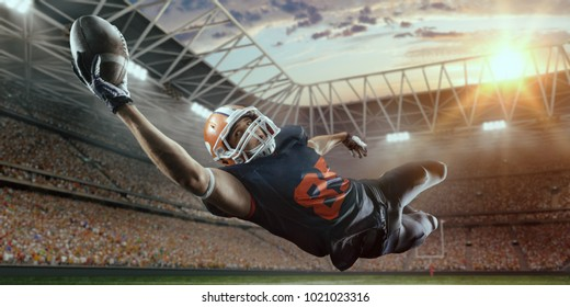 American football player jumps and catches the ball in flight in professional sport stadium