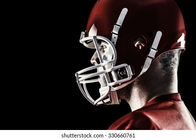 American football player looking at camera against black