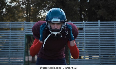 American football player man putting on helmet and looking at camera.