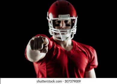 American football player pointing at camera on black background