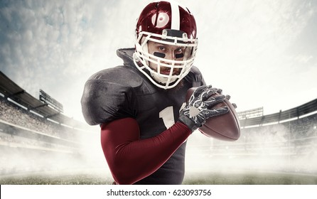American football player posing with ball on stadium background - Super Bowl concept