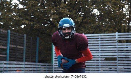 American football player practising throwing ball during training then looking to camera.