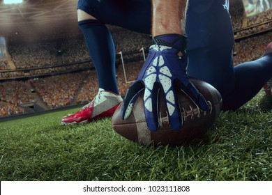 American football player in professional sport stadium. Close-up hand, ball, legs