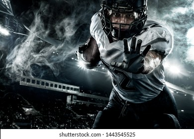 American football player. Sportsman with ball in helmet on stadium in action. Sport wallpaper. Closeup portrait.