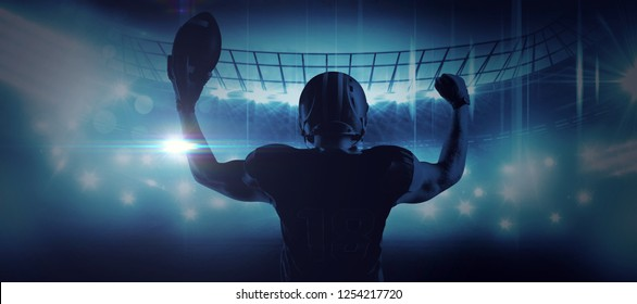 American football player standing with helmet holding football in victory against american football arena