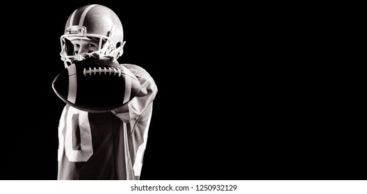 American football player standing with rugby ball and helmat against black background