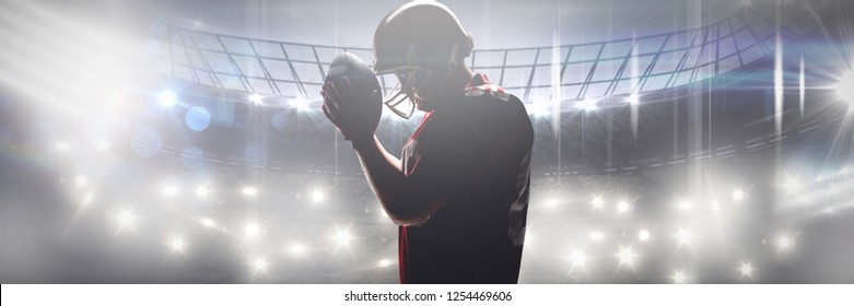 American football player standing with rugby helmet and ball against american football arena