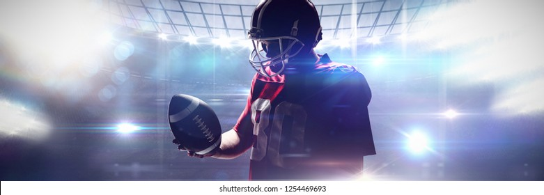American football player standing with rugby ball and helmet against american football arena
