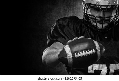 American football player standing with rugby helmet against black background