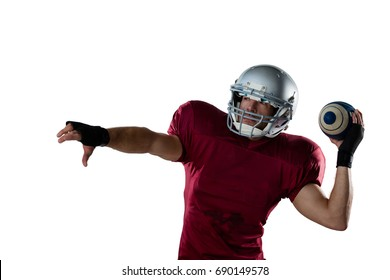 American football player wearing helmet throwing ball against white background