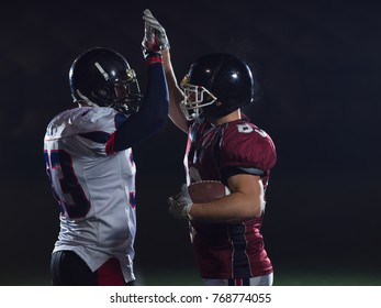 american football players giving high fives after scoring a touchdown on field at night