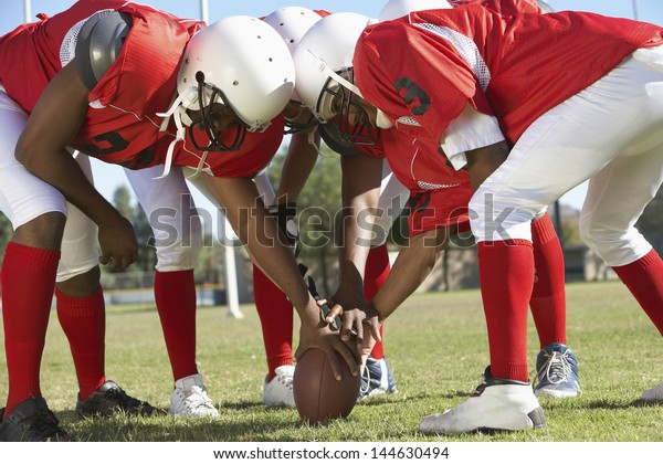 American football players in a huddle around the ball on field
