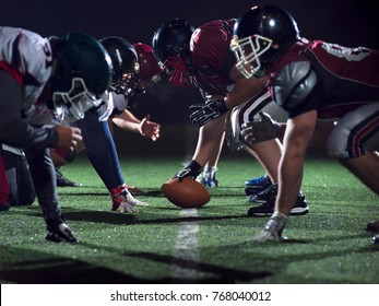 american football players are ready to start on field at night