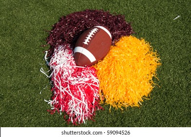 American football and pom poms on field.