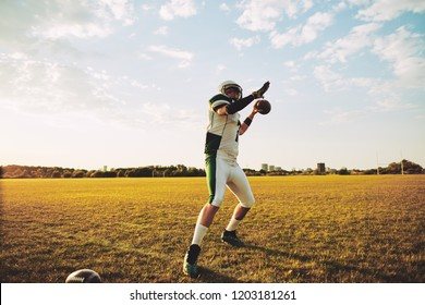 American football quarterback about to throw a football during team practice drills on a sports field in the afternoon