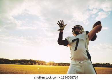 American football quarterback about to throw a pass during team practice drills on a football field in the afternoon